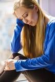Muchacha adolescente deprimida triste que se sienta en travesaño de la ventana Fotografía de archivo libre de regalías
