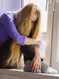 Muchacha adolescente deprimida triste que se sienta en travesaño de la ventana Foto de archivo