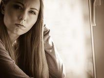 Muchacha adolescente deprimida triste que se sienta en travesaño de la ventana Imagenes de archivo