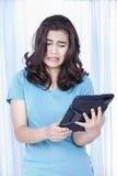 Muchacha adolescente disgustada en la tablilla del ordenador Fotos de archivo libres de regalías