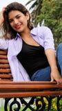 Muchacha adolescente diversa y felicidad que se sientan en banco Foto de archivo