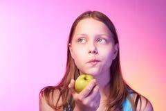 Muchacha adolescente divertida emocional que come la manzana Imágenes de archivo libres de regalías