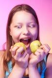 Muchacha adolescente divertida emocional que come la manzana Foto de archivo libre de regalías