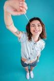 Muchacha adolescente divertida joven que estira y que juega con la goma buble Fotografía de archivo