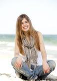 Muchacha adolescente divertida que se sienta cerca del mar. Foto de archivo libre de regalías