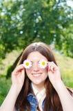 Muchacha adolescente divertida que sostiene las flores de la margarita en sus ojos Foto de archivo libre de regalías