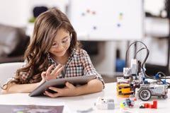 Muchacha adolescente divertida que usa la tableta en el estudio de la ciencia Fotografía de archivo