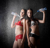 Muchacha adolescente dos que vierte de la botella en estudio del agua Imagenes de archivo