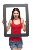 Muchacha adolescente emocionada que mira a través de marco, Fotografía de archivo