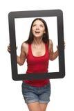 Muchacha adolescente emocionada que mira a través de marco Foto de archivo