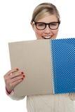 Muchacha adolescente emocionada que sostiene el cuaderno cerca de ella Foto de archivo