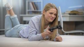 Muchacha adolescente emocional que juega al videojuego en el tiempo libre, trastorno por fracaso virtual almacen de video