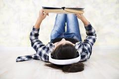 Muchacha adolescente en auriculares que lee un libro Fotos de archivo