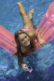 Muchacha adolescente en bikiní rosado en un flotador Fotografía de archivo