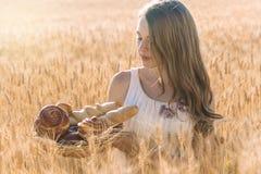 Muchacha adolescente en campo del centeno con la cesta de bollos Foto de archivo libre de regalías