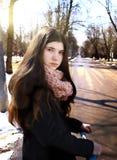 Muchacha adolescente en capa negra y pelo marrón largo con el schooter Fotos de archivo libres de regalías