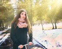 Muchacha adolescente en capa negra y pelo marrón largo con el schooter Foto de archivo