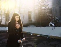 Muchacha adolescente en capa negra y pelo marrón largo con el schooter Foto de archivo libre de regalías