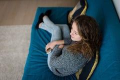 Muchacha adolescente en casa que se sienta en el sofá, piernas cruzadas Imagenes de archivo