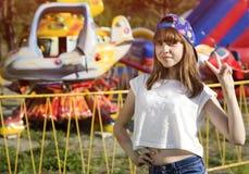 Muchacha adolescente en casquillo en el parque de atracciones Imágenes de archivo libres de regalías