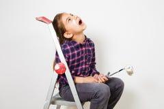 Muchacha adolescente en dreamin de la escalera del edificio con un cepillo para pintar en la pared blanca Imagen de archivo libre de regalías