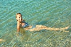Muchacha adolescente en el agua de mar costera Imagen de archivo