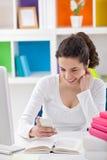 Muchacha adolescente en el escritorio con el teléfono Foto de archivo libre de regalías