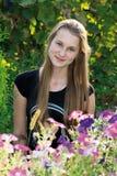 Muchacha adolescente en el fondo de flores Foto de archivo libre de regalías
