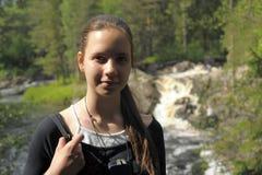 Muchacha adolescente en el fondo de una cascada Fotos de archivo