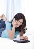 Muchacha adolescente en el ordenador y el teléfono de la tablilla Foto de archivo