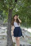 Muchacha adolescente en el parque que mira la cámara que hace muecas Foto de archivo