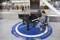 Muchacha adolescente en el piano de cola para que todo el mundo utilice en el pasillo de la central Foto de archivo libre de regalías