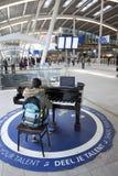 Muchacha adolescente en el piano de cola para que todo el mundo utilice en el pasillo de la central Fotografía de archivo