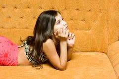 Muchacha adolescente en el sofá Foto de archivo libre de regalías