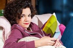 Muchacha adolescente en el sofá con el teléfono elegante. Fotografía de archivo