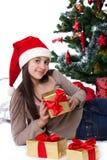 Muchacha adolescente en el sombrero de Papá Noel con los regalos debajo del árbol de navidad Fotografía de archivo libre de regalías