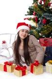 Muchacha adolescente en el sombrero de Papá Noel con los regalos debajo del árbol de navidad Fotos de archivo