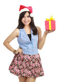 Muchacha adolescente en el sombrero de Santa que presenta el regalo Foto de archivo