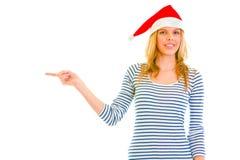 Muchacha adolescente en el sombrero de Santa que señala en esquina Fotos de archivo