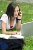Muchacha adolescente en el teléfono que coloca en la hierba Foto de archivo libre de regalías