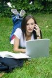 Muchacha adolescente en el teléfono que coloca en la hierba Fotografía de archivo