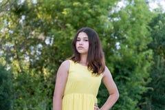 Muchacha adolescente en el vestido amarillo que se coloca en el parque Foto de archivo