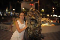 Muchacha adolescente en el vestido blanco al lado de la escultura de un león Imagen de archivo