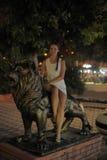 Muchacha adolescente en el vestido blanco al lado de la escultura de un león Fotos de archivo libres de regalías