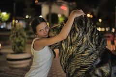 Muchacha adolescente en el vestido blanco al lado de la escultura de un león Foto de archivo libre de regalías