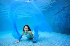 Muchacha adolescente en el vestido que presenta bajo el agua en la parte inferior de la piscina, jugando con un paño azul, mirand Foto de archivo libre de regalías