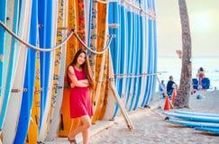Muchacha adolescente en el vestido rojo que se inclina por las tablas hawaianas en la playa Imagenes de archivo