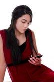 Muchacha adolescente en el vestido rojo que sostiene el teléfono móvil Imagen de archivo