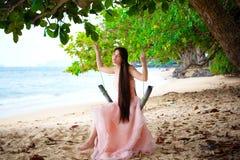 Muchacha adolescente en el vestido rosado que se sienta en el oscilación en la playa Foto de archivo libre de regalías