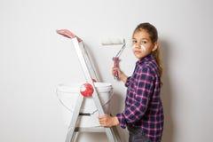Muchacha adolescente en escalera del edificio usando un cepillo para pintar en el w Fotos de archivo libres de regalías